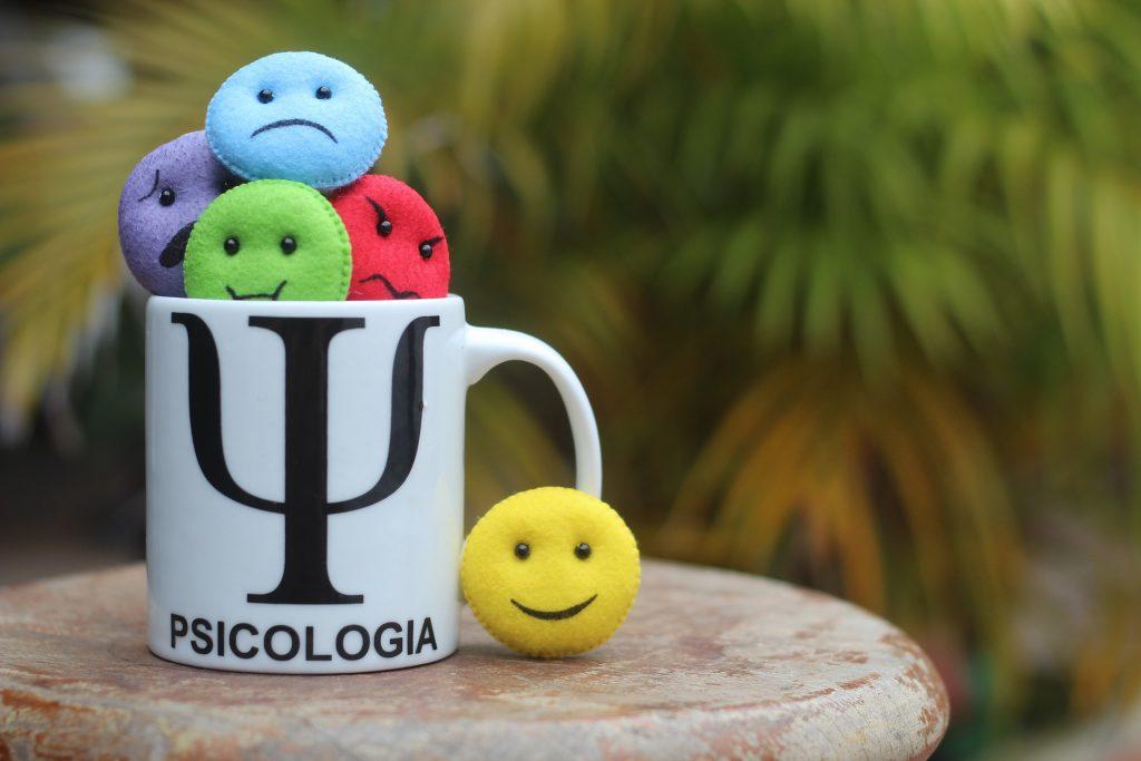 En una taza en la que pone psicología se apelotonan pequeños emoticonos con las distintas emociones. Fuera, está el emoticono de la alegría.