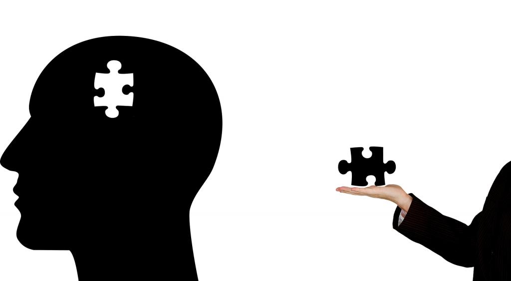 una mano sujeta una pieza de puzzle, que es la que falta en una cabeza que tiene al lado.