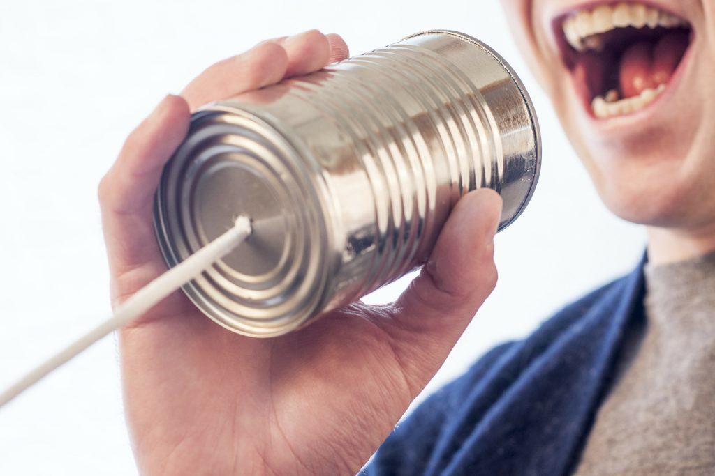 Un niño habla a una lata con un cordón en su base a modo de teléfono